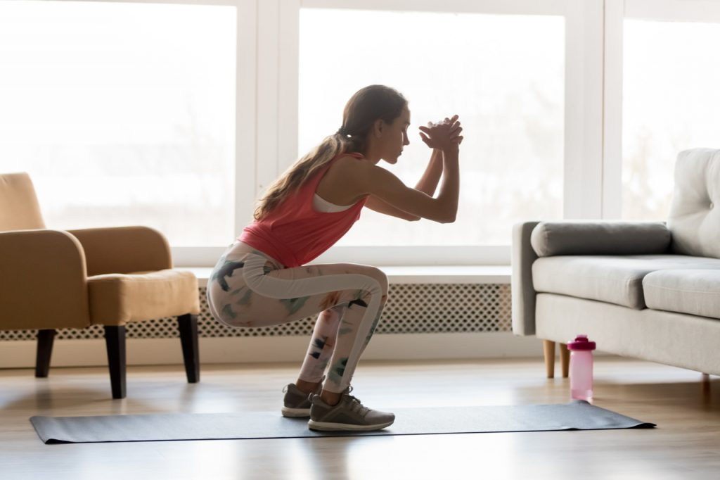 Sporty young woman doing squat morning exercise alone in living room.