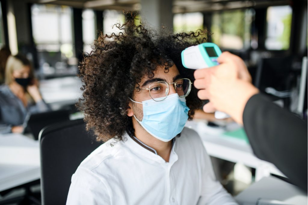 Young man with face mask back at work in office after lockdown, measuring temperature.