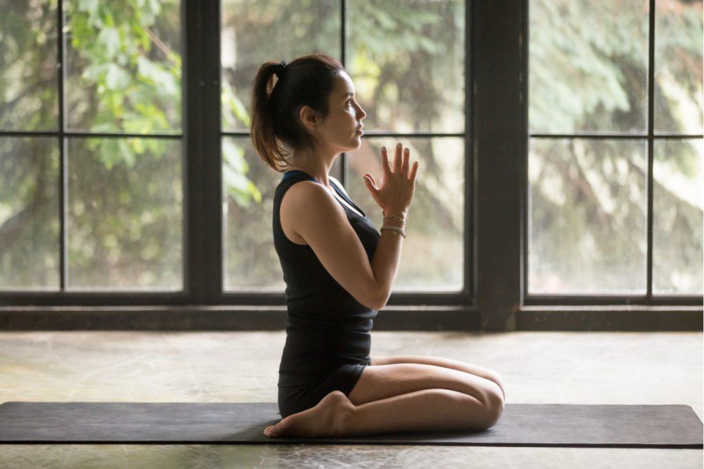 Woman practicing yoga at home, sitting in virasana pose.