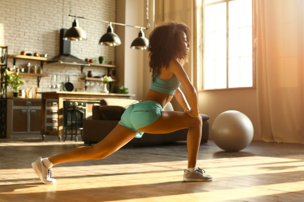Sporty woman training doing lunges at home.
