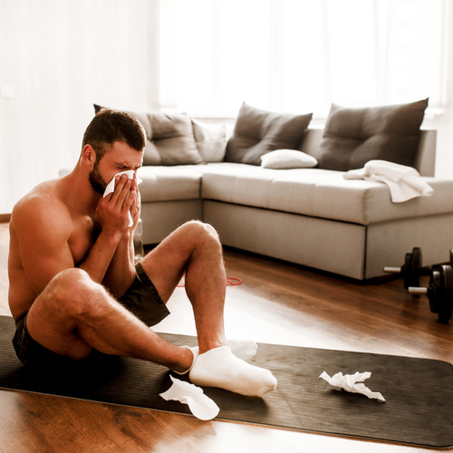 Sick man doing yoga sit on mat and sneeze into white tissue.