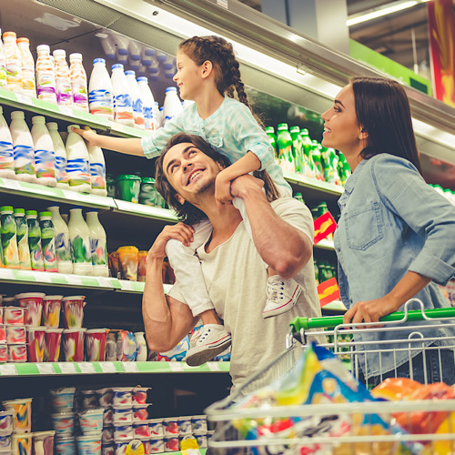 young parents and their cute little daughter are smiling while choosing food in the supermarket.