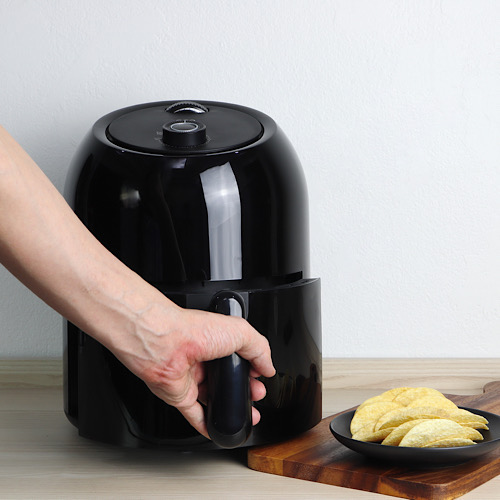 a black air fryer or oil free fryer appliance on the wooden table in the kitchen is holded by hands with deep fried potato chips in the black dish on the wooden tray