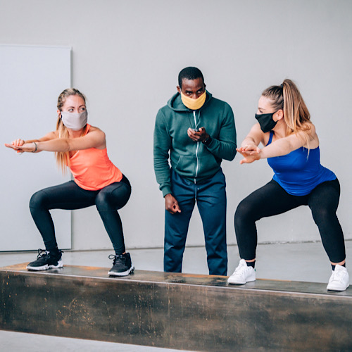Two girls exercising with a personal trainer at the gym with protective mask in pandemic period of covid1