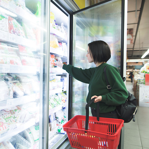 A girl with a basket takes frozen foods from the supermarket's refrigerator.
