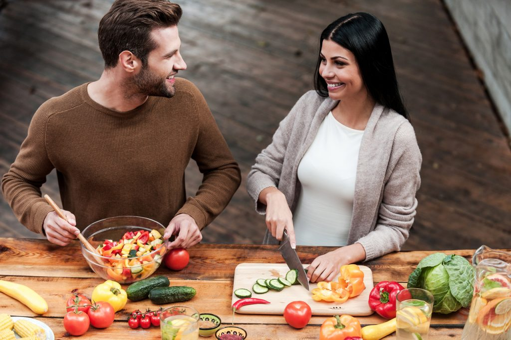 A couple preparing healthy food in the kitchen, adopting the Mediterranean diet, one of the health and wellness food trends.