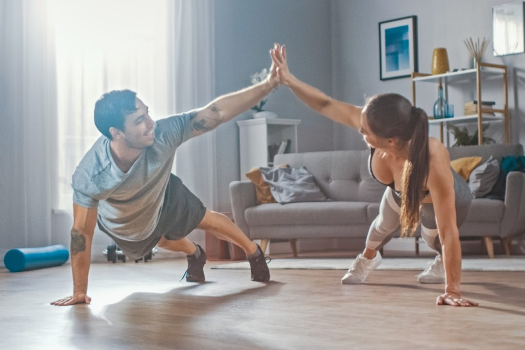 Athletic Fitness Couple in Workout Clothes Doing Push Up Exercises and Giving Each Other a High Five.