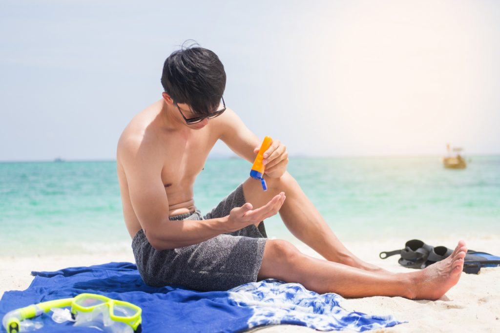 Man applying sunblock lotion to self at the beach.