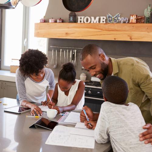 Parents Helping Children With Homework In Kitchen.