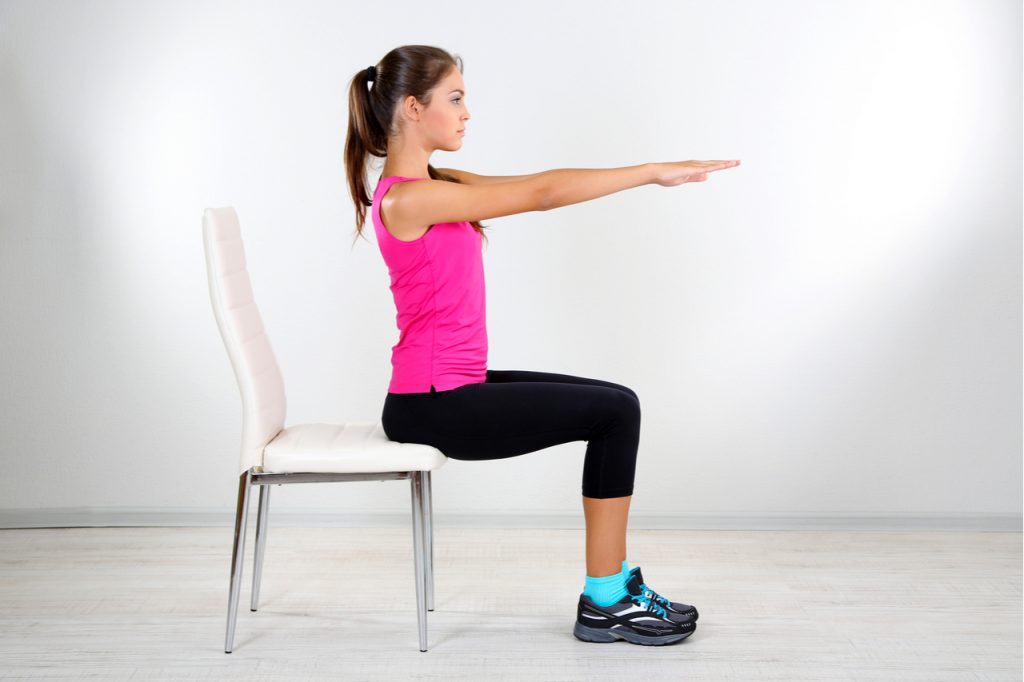 A young fit woman doing chair squats.