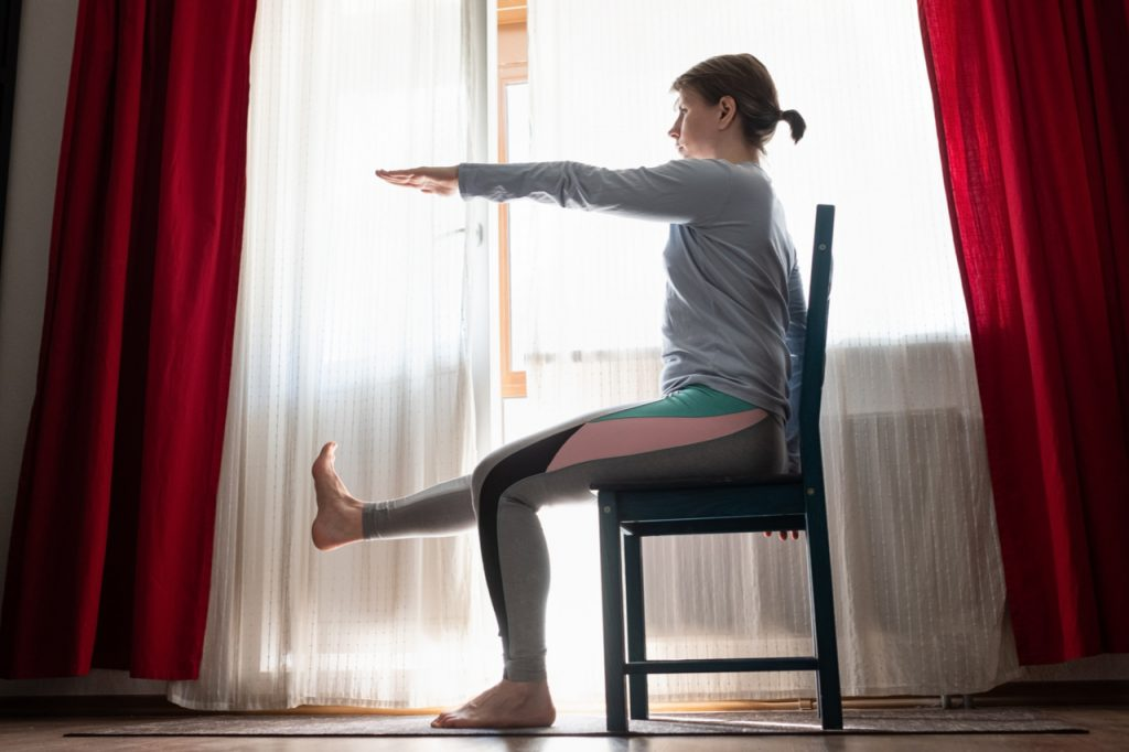 Woman doing exercises at home sitting on chair.