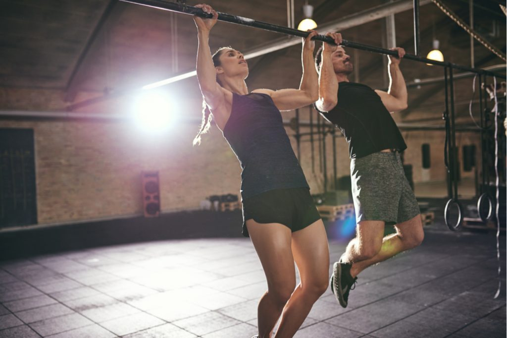 A couple doing pull-ups.