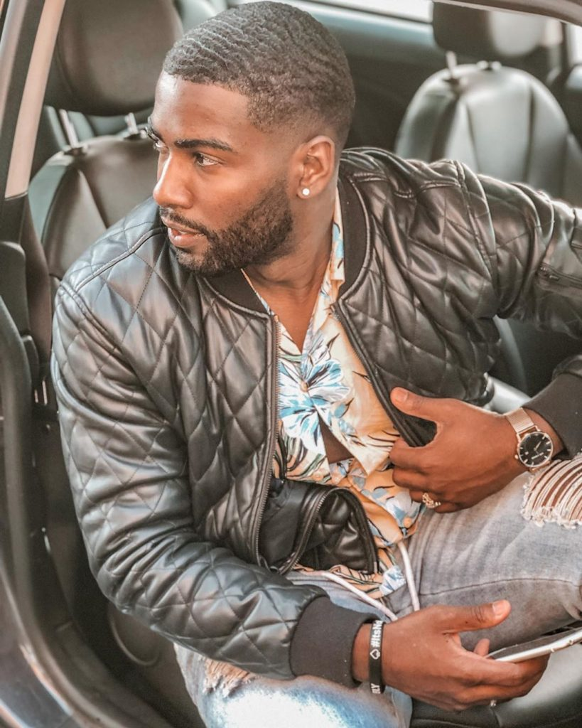 Donny Savage wearing a black leather jacket getting out of a car.