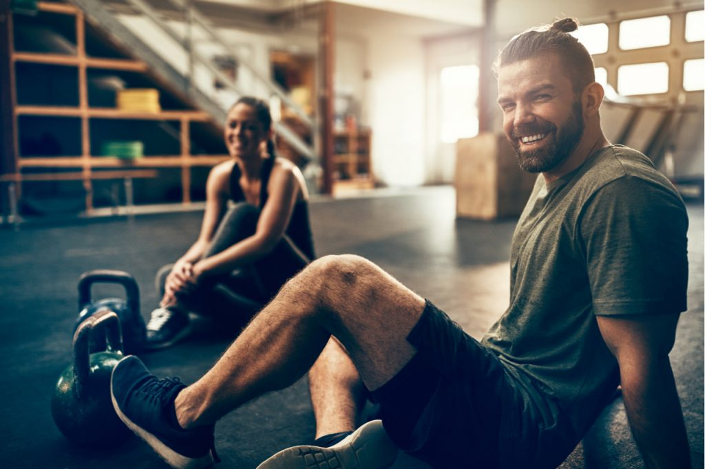 Fit people in exercise gear sitting together on the floor of a gym laughing together after a workout.