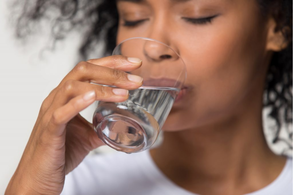 Close up focus on female drinking a glass of water in between drinking low calorie cocktail to try this labor day.