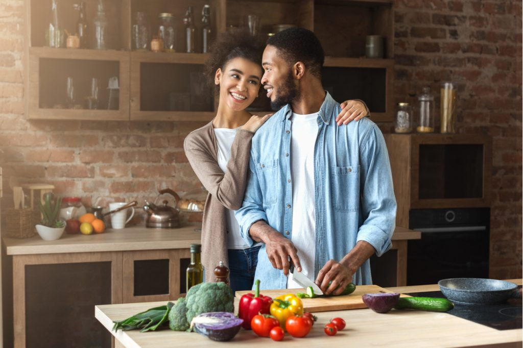 Loving couple preparing salad in loft kitchen at home.