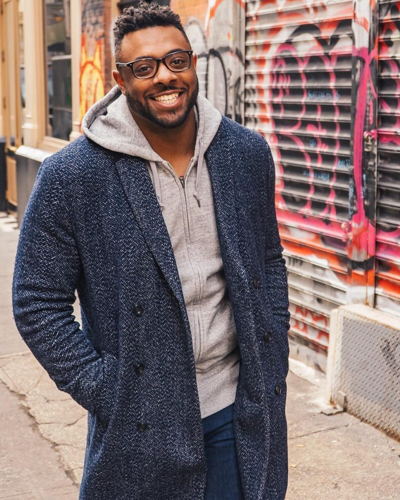 A photo of Eric Dunn wearing an overcoat and a gray hoodie with a smile on his face.