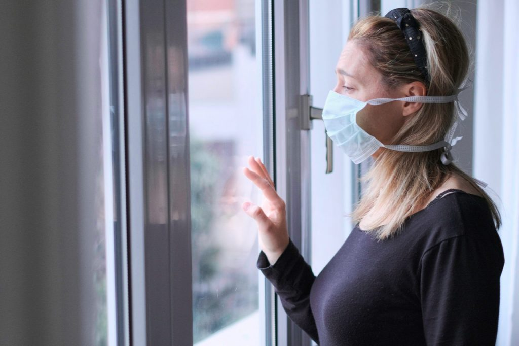 A woman wearing a mask looking through the window while at home looking stressed which is one of the few covid-19 emotions.