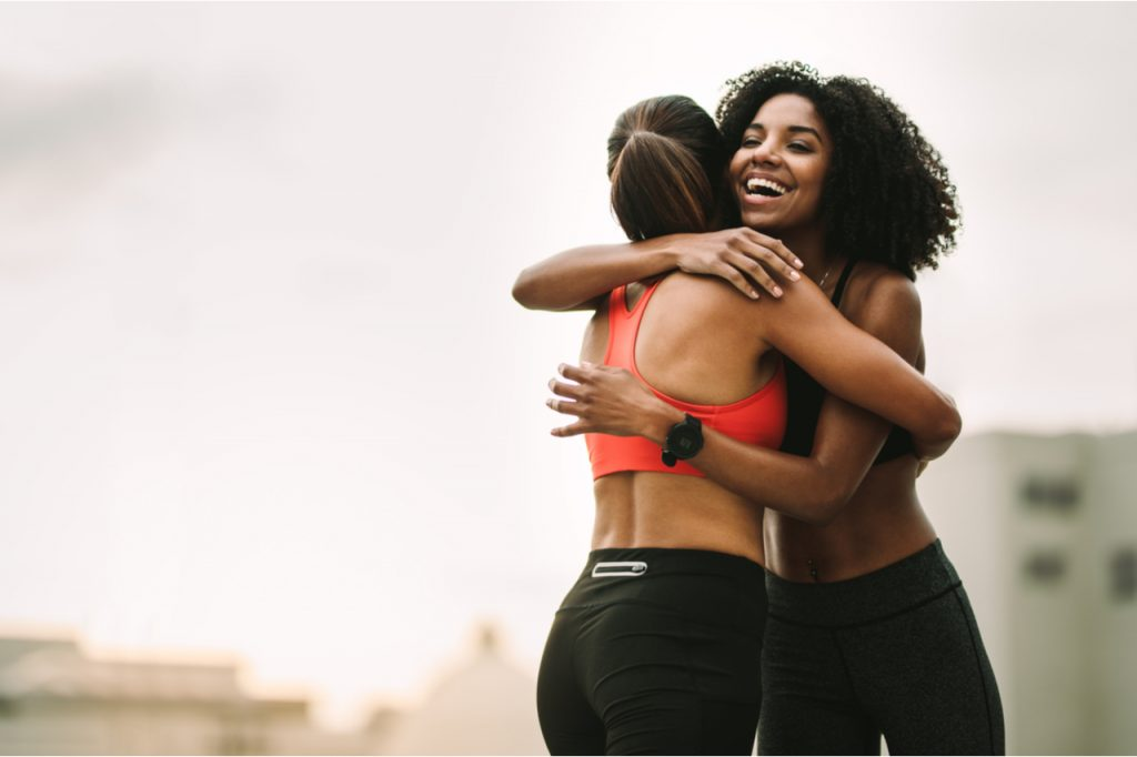 Cheerful female athletes embracing each other after workout.