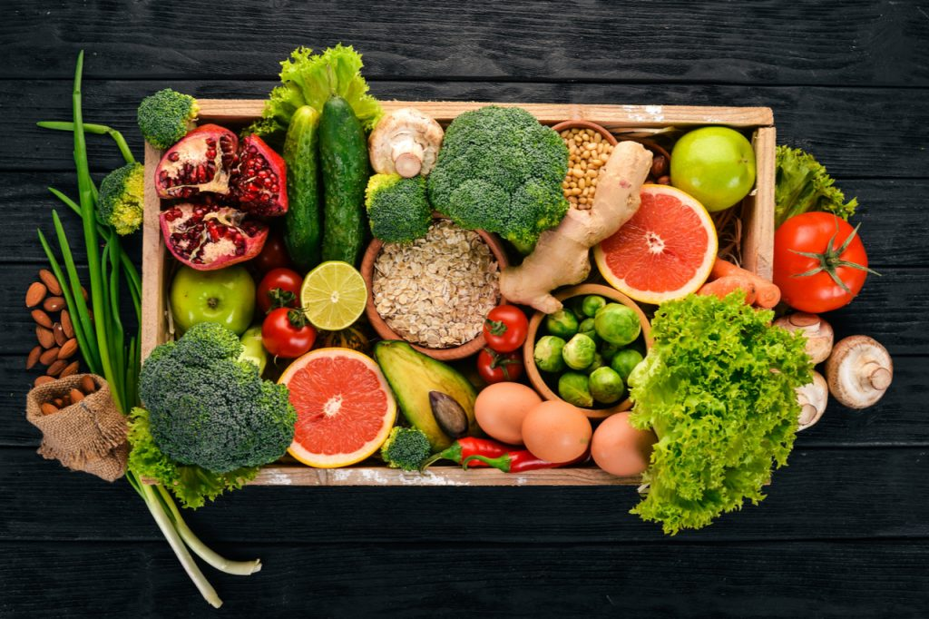 Fresh seasonal food vegetables, nuts and fruits in a wooden box.