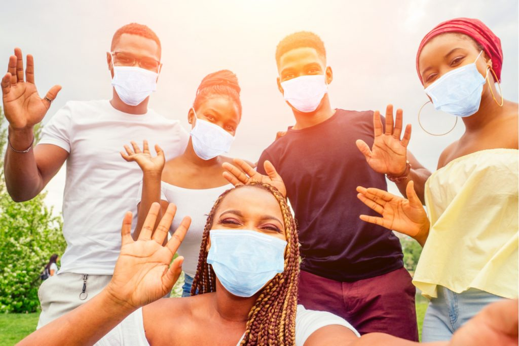 Group of five friends female and male in medical mask taking selfie on camera smartphone and having fun outdoors.