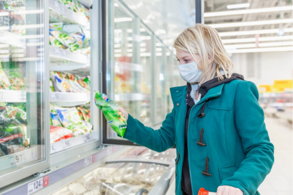 A woman at a supermarket checking on a frozen food.