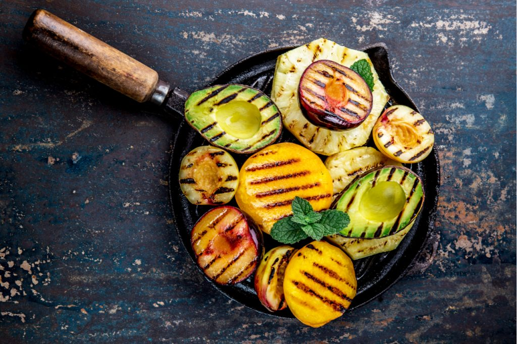 Grilled avocado, peaches, pineapple,   and plums on a black cast iron pan.