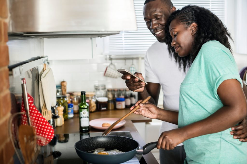Couple cooking fried eggs in the kitchen which would be healthier when done using newair air fryer.