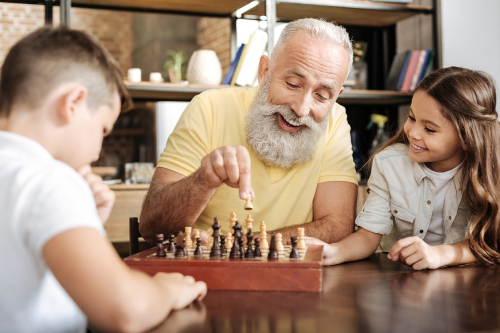 Little girl watching her brother and grandfather play chess.
