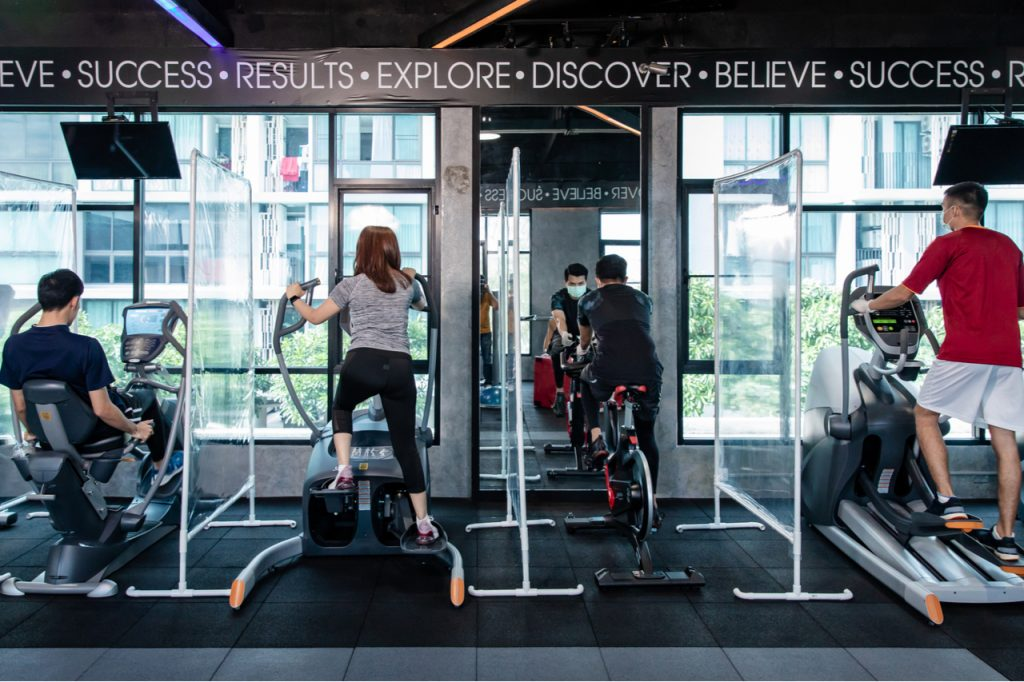 A few people working out at the gym. The gym uses barriers in between gym equipment to ensure safety and social distancing.