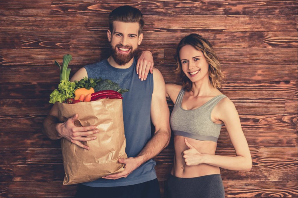 Couple in sportswear is holding a shopping bag full of healthy food.
