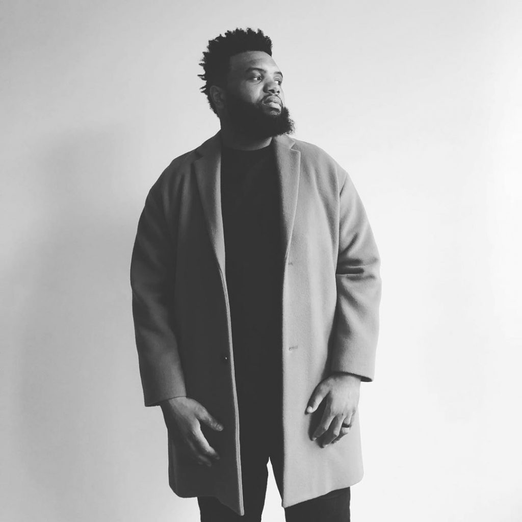 A black and white or grayscale shot of Jeff Allen wearing a coat and black shirt