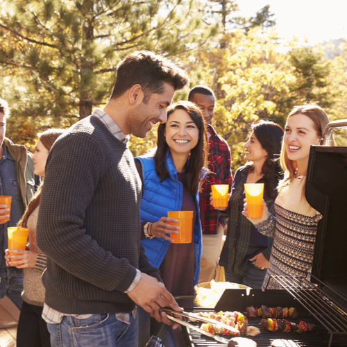 Group of friends stand at a barbecue, one cooking at grill.