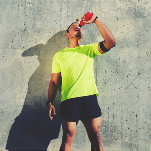 Young tired athlete refreshing with energy drink while standing against cement wall.