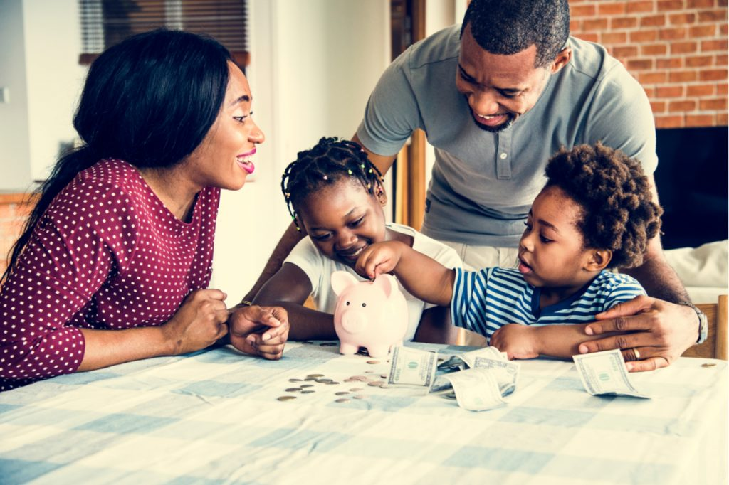 Family saving money to piggy bank learning what is financial wellness.