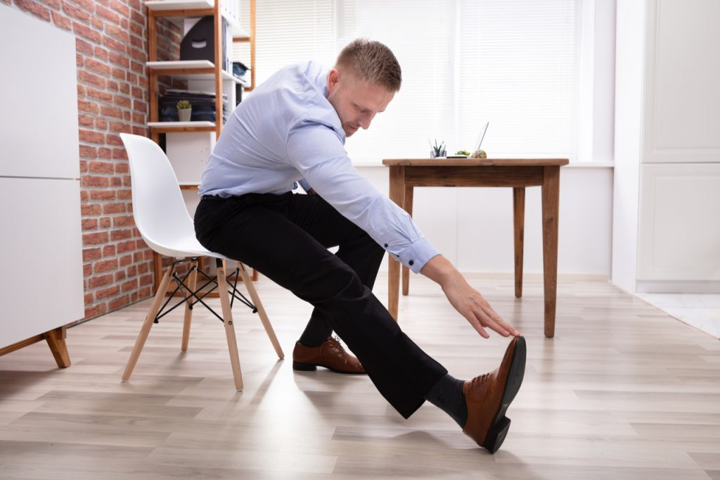 Businessman Sitting On White Chair doing chair exercise.