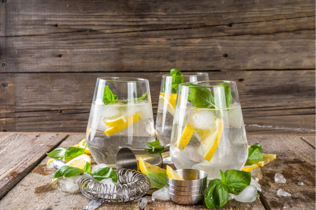 A lemon-based fruity alcoholic drink topped with basil and ice.