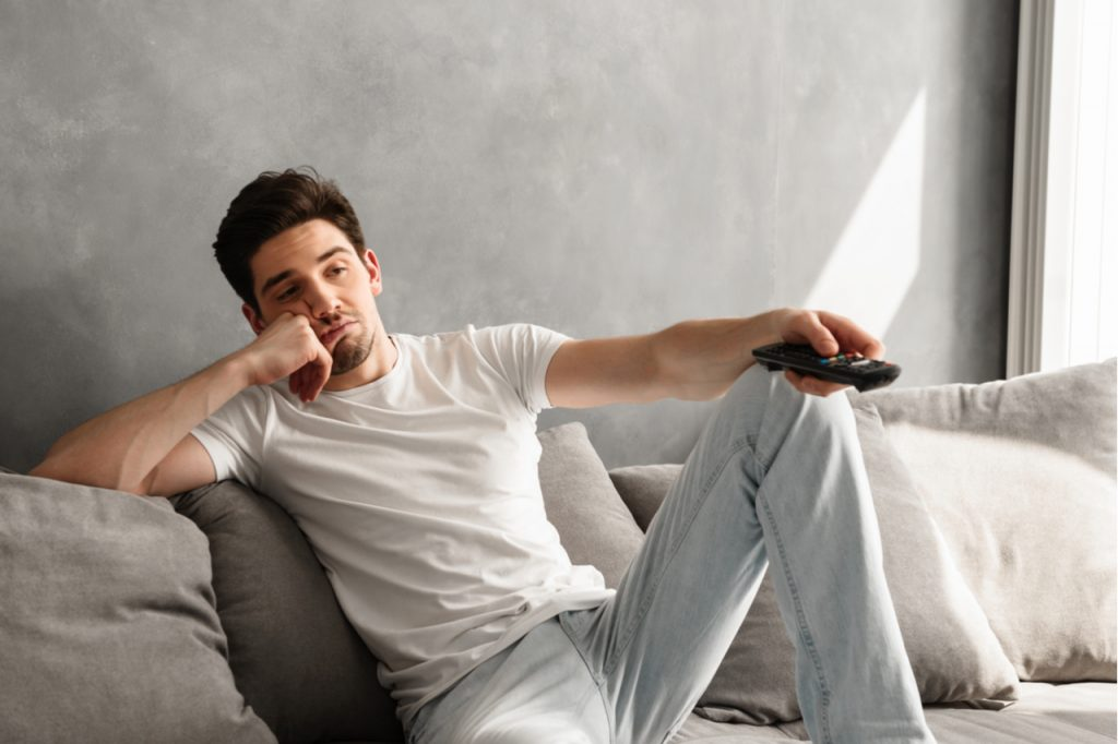 A man sitting on the couch looking bored while watching TV at home.