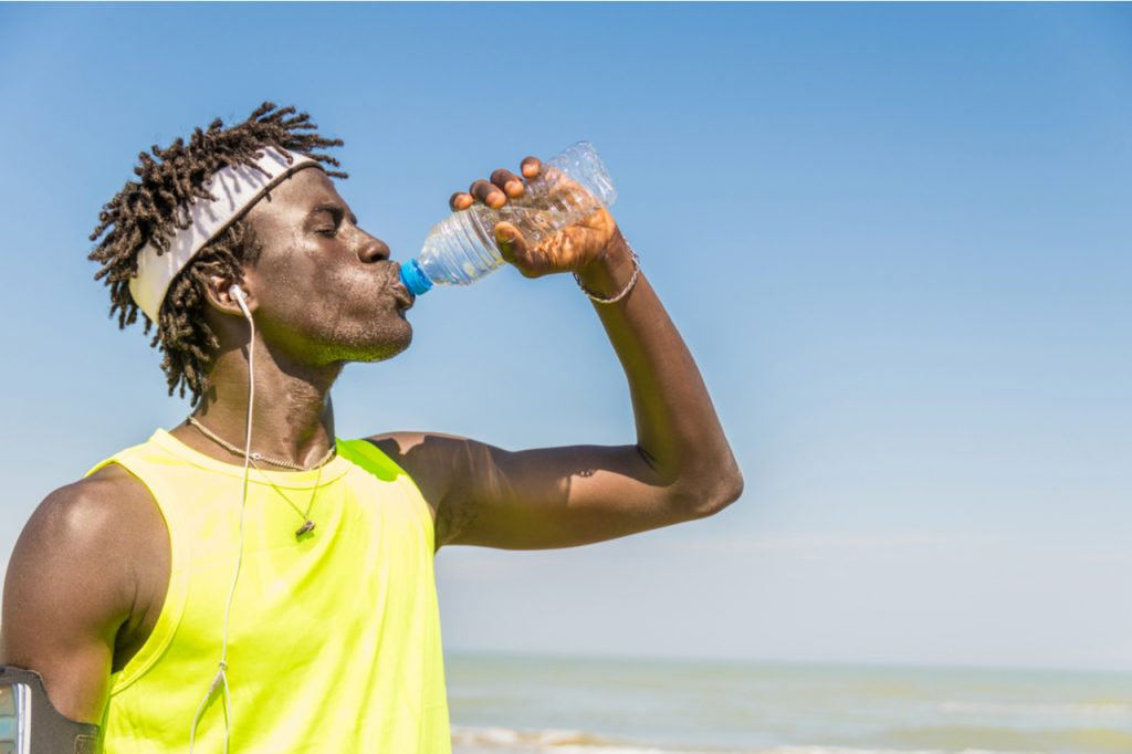A fit looking man drinking water by the beach, taking a break from jogging.