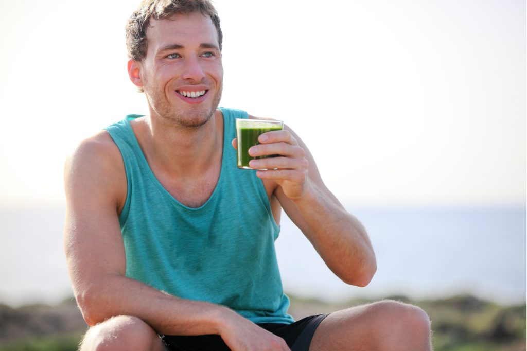 Man drinking ladder superfood greens outdoors before a workout.