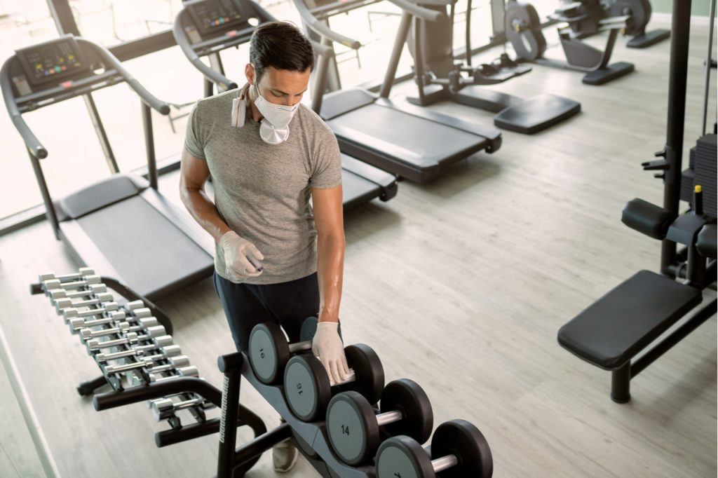 A man wearing a face mask wiping and disinfecting gym equipment.