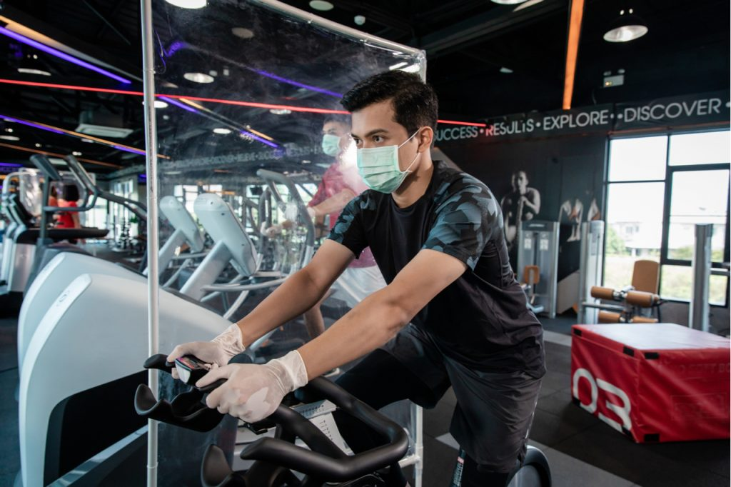 Asian man working out on a stationary bike at the gym while wearing a mask. The gym uses plastic barriers in between workout equipment as part of the new normal.