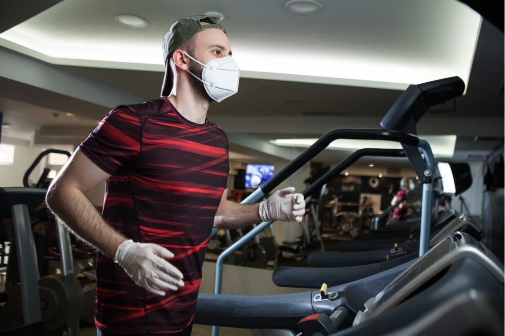 A man wearing gloves and a face mask running on a treadmill at the gym.