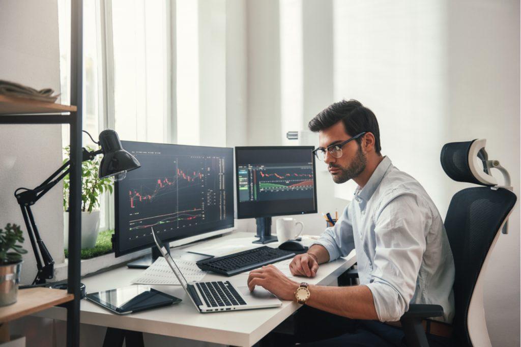 Busy man looking in his computer, understanding the stock market.