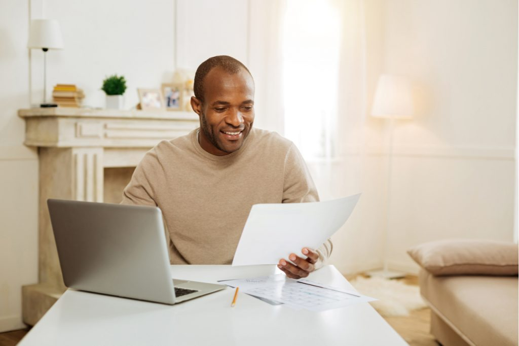 An Afro-American man in front of his laptop, holding some papers on his hand while working from home - one of his financial resources.