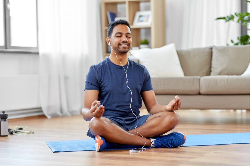 Man in earphones listening to music on smartphone and meditating in lotus pose at home for positive energy.