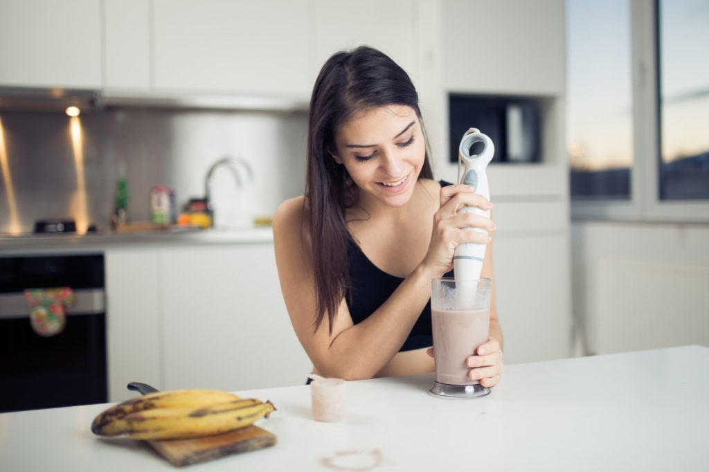 Woman with hand blender making sweet banana cocoavia liquid supplement protein powder milkshake smoothie.