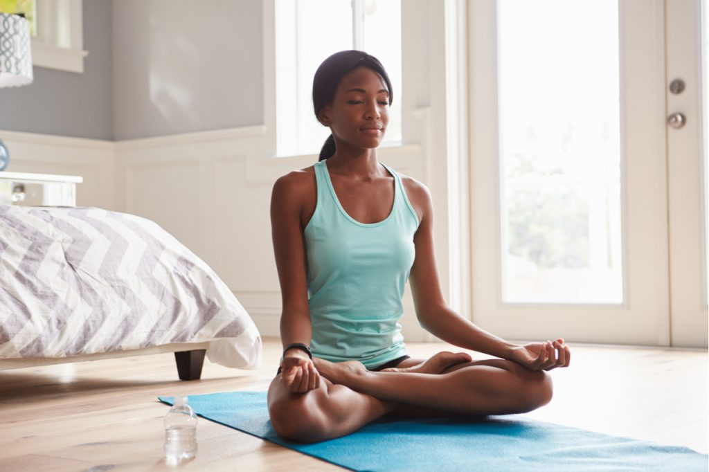 Young woman doing yoga as a morning  routine at home in the lotus position.