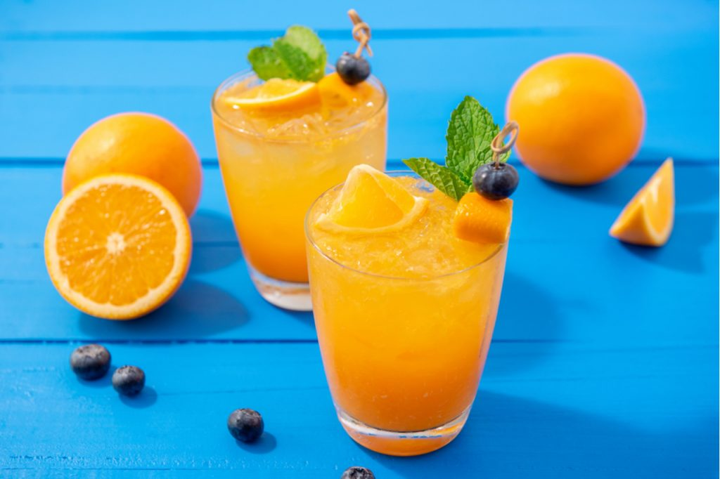 Two orange cocktails on a blue table.