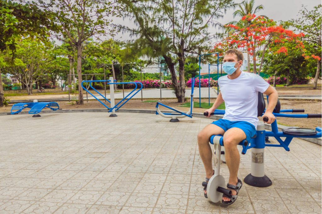 Man working out at the park using a leg machine.